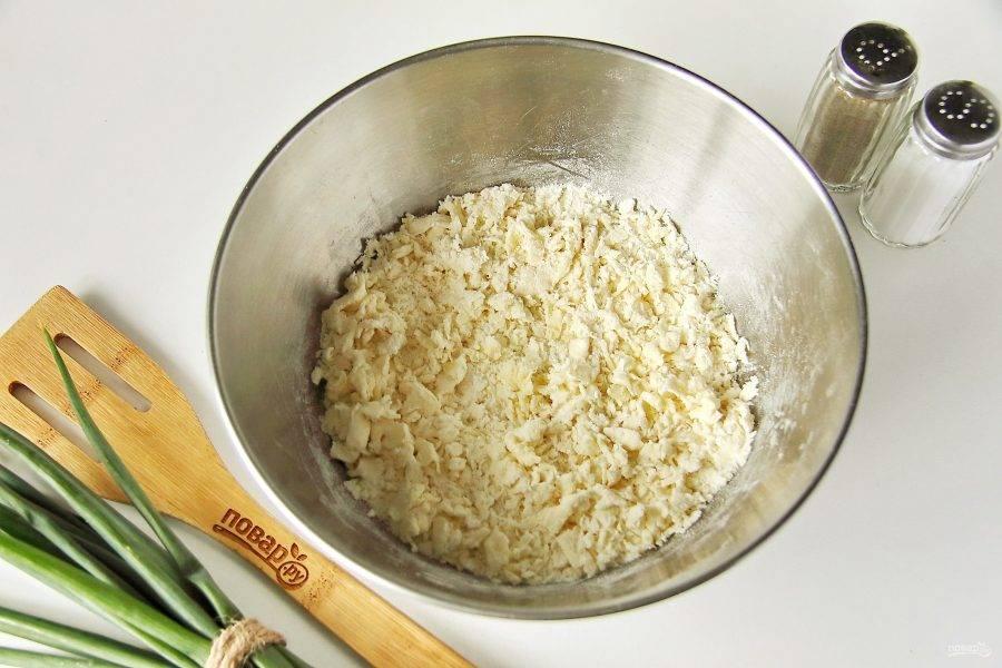 Соедините муку и сливочное масло. Добавьте 0,5 ч.л. соли и перетрите все руками в крошку.