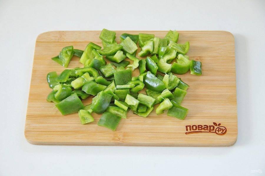 Перец разрежьте пополам, удалите семена и нарежьте кубиками. Обжарьте до мягкости.