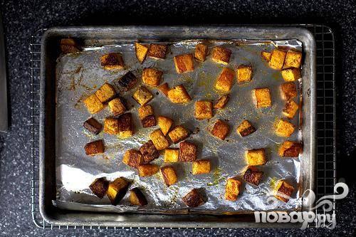 2. Перемешать кубики тыквы с 2 столовыми ложками оливкового масла, тмином, паприкой и солью. Выложить смесь в один слой на противень и запекать 20 минут. Перевернуть и жарить еще 10-15 минут, до готовности. Дать остыть.