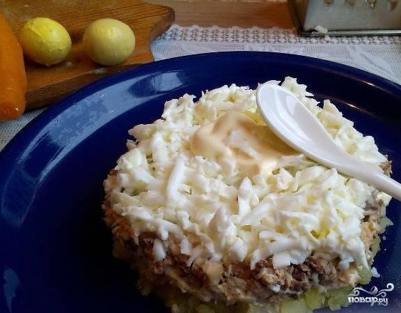 4. Сваренные вкрутую яйца разделите на желток и белок. В следующем слое понадобится только белок. Натрите его на терке и выложите поверх сардин. Слой белка смажьте майонезом.