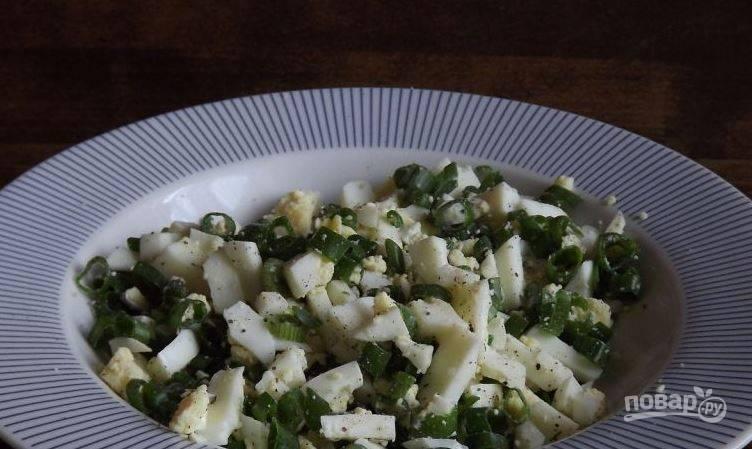 Пока тесто отдыхает, приготовьте начинку. Для этого отварите вкрутую куриные яйца, остудите их, очистите от скорлупы и нарубите кубиками. Добавьте к ним мелко нарезанный зеленый лук, соль и перец. Все тащательно перемешайте.