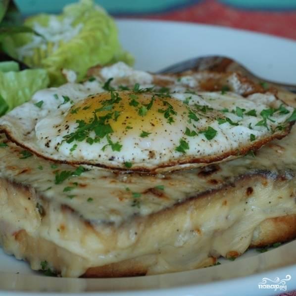 Обжаренное яйцо кладем на наш запеченный бутерброд, посыпаем зеленью - и крок-мадам готов. Подавать горячим.
