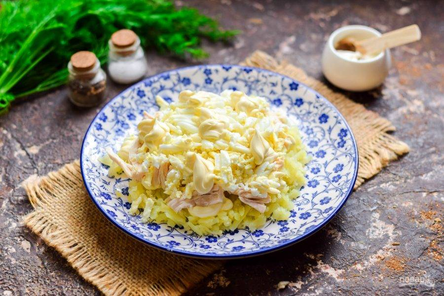 Куриные яйца отварите вкрутую, очистите и натрите на средней терке. Выложите яйца поверх курицы, смажьте майонезом.