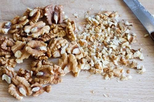 4. Нарезаем орехи (предпочтительно, грецкие). Лучше шинковать их крупнее. Некоторые любят измельчать блендером - по вашим вкусовым предпочтениям.