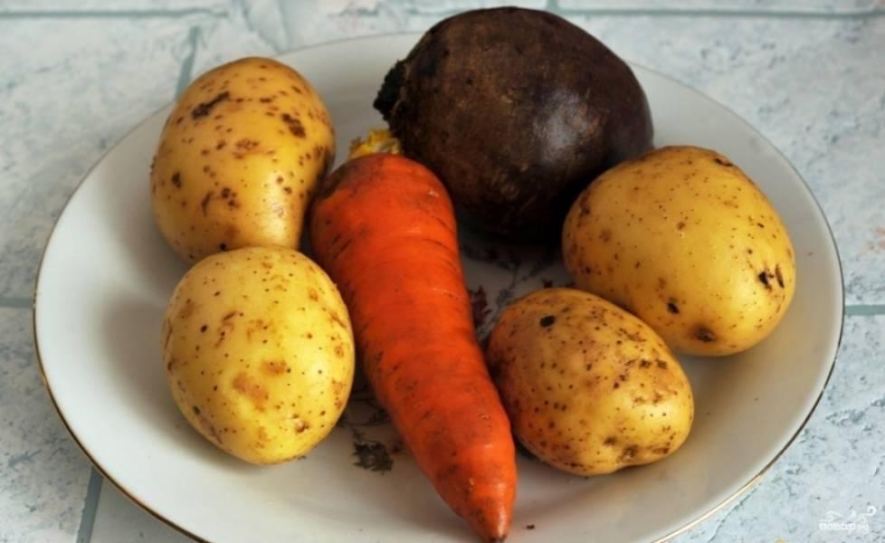 1.Перед тем, как приготовить горячий винегрет, вымойте морковь, свеклу и картофель. Очистите от грязи. Старайтесь при этом не нарушать кожицу на овощах. Налейте в кастрюлю холодной воды. Положите овощи. Варите до готовности.
