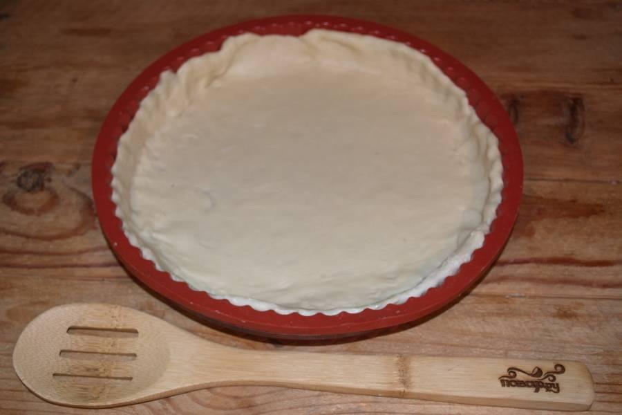 Форму нужно смазать маслом. Выложите тесто в форму, создайте бортики.