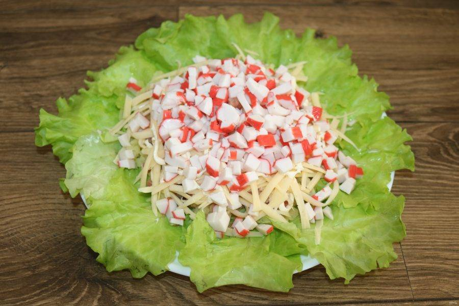 Затем выложите нарезанные крабовые палочки,  посыпьте мелко нарезанным укропом, сделайте сеточку майонеза.