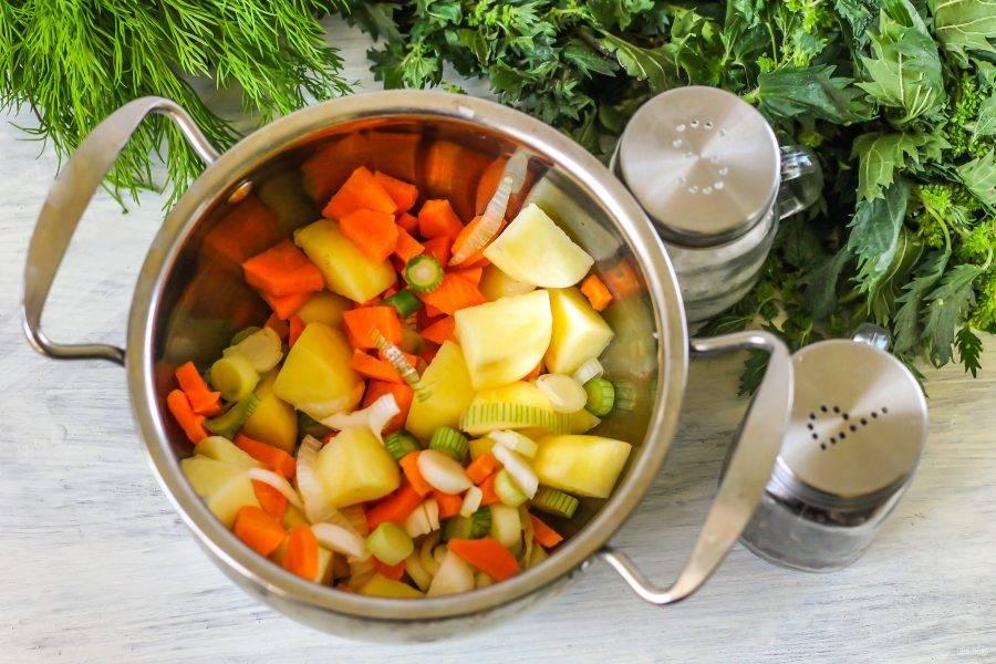 Овощи очистите от кожуры, промойте в воде и нарежьте картофель на четыре части, лук - полукольцами, а морковь натрите на терке с мелкими ячейками. Выложите все нарезки в кастрюлю.
