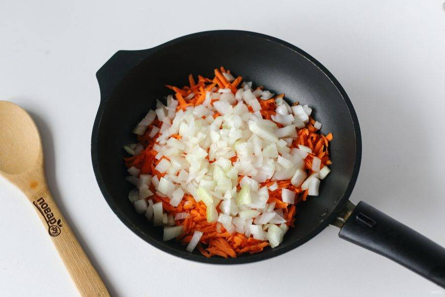 Разогрейте сковороду с маслом. Выложите тертую морковь и нарезанный кубиками лук.