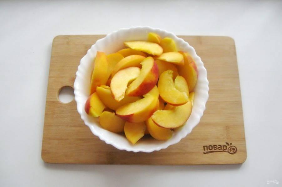 Персики помойте, удалите косточку и нарежьте дольками.