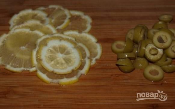 Тонкими кольцами режем лимон и оливки.