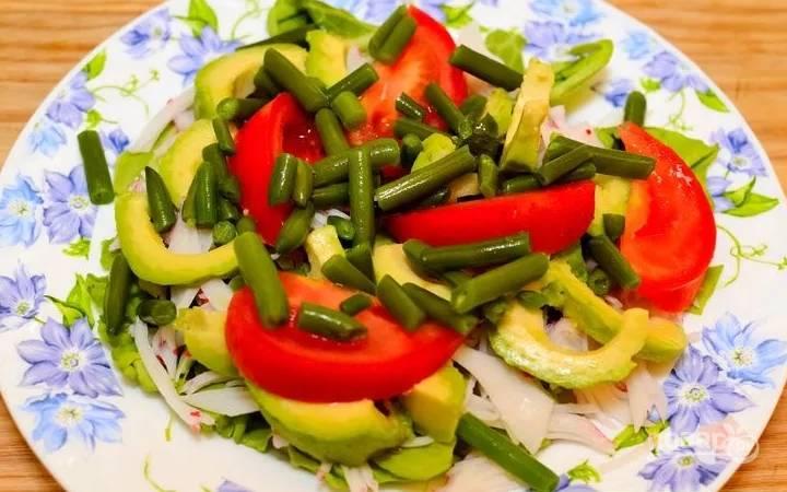 3.Авокадо очищаю и нарезаю ломтиками, томаты мою и нарезаю дольками, а спаржевую фасоль отвариваю немного. Выкладываю ингредиенты на салат: сперва крабовое мясо, затем авокадо, помидоры и фасоль.