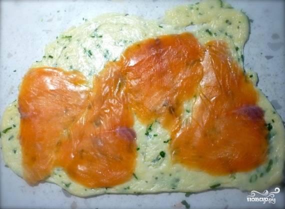 5. Расстелите пищевую пленку и выложите на него равномерно сырную массу. Накройте сверху вторым куском пищевой пленки. Раскатайте до формы прямоугольника. Снимите верхнюю пленку. Выложите кусочки семги на сырный прямоугольник так, чтобы не было нахлестов.
