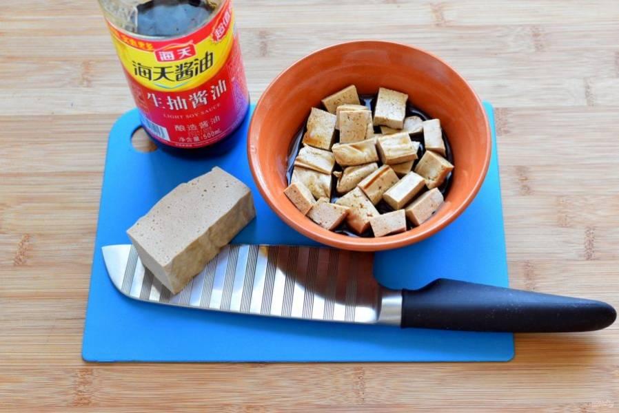 Тофу нарежьте небольшими кубиками и замаринуйте в соевом соусе на 10 минут.