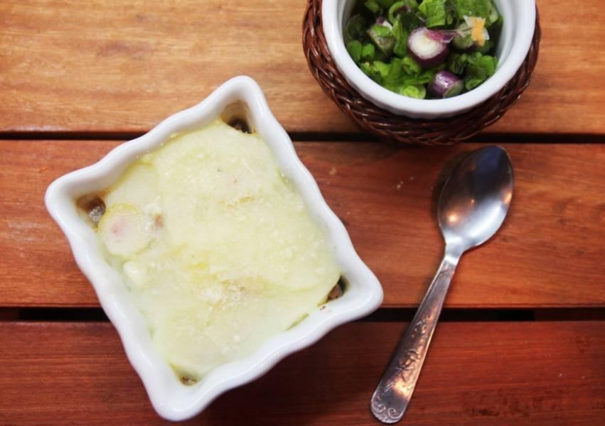 Сверху залейте картофельным пюре, посыпьте сверху тертым сыром. Выпекайте в духовке около 15 минут, пока сыр не станет золотисто-коричневого цвета.