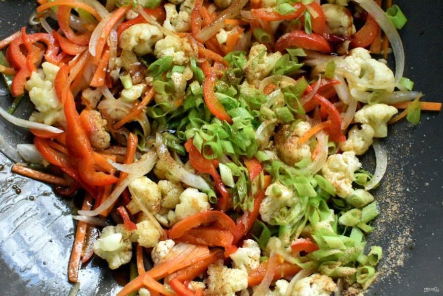 Полейте овощи соевым соусом, добавьте пряности, кунжутное масло и шинкованный зеленый лук. Хорошо перемешайте и тушите в течение нескольких минут.