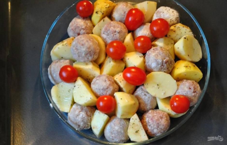 Выложите фрикадельки и помидоры к картофелю. Уберите запекаться ингредиенты в духовку на 10 минут при 180 градусах.