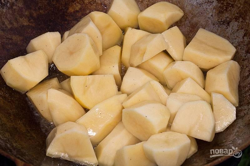 Картофель почистите, промойте и крупной нарежьте. Отправьте его в казан на костре с маслом. Обжарьте до золотистого цвета, после чего уберите из казана.