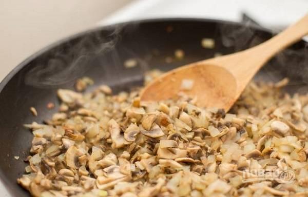 3. Вымойте и измельчите грибы. Жарьте минут 10, периодически помешивая. Когда жидкость полностью испарится, добавьте муку и тщательно перемешайте, чтобы не образовались комочки.