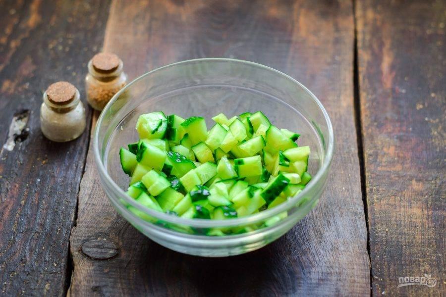 Огурец сполосните и просушите, нарежьте небольшими кубиками и переложите в салатник.