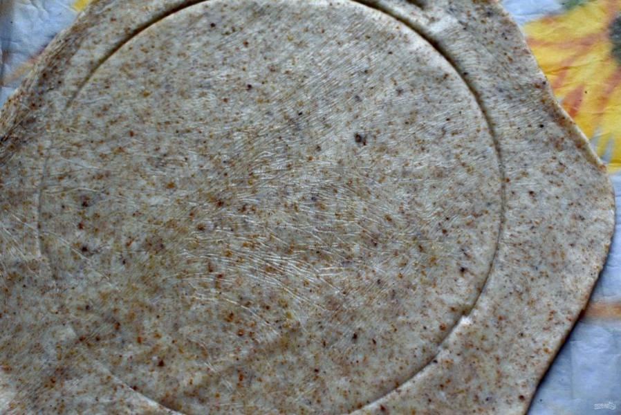 Круглой миской подходящего диаметра наметьте круг по центру. Так будет удобнее выкладывать начинку.