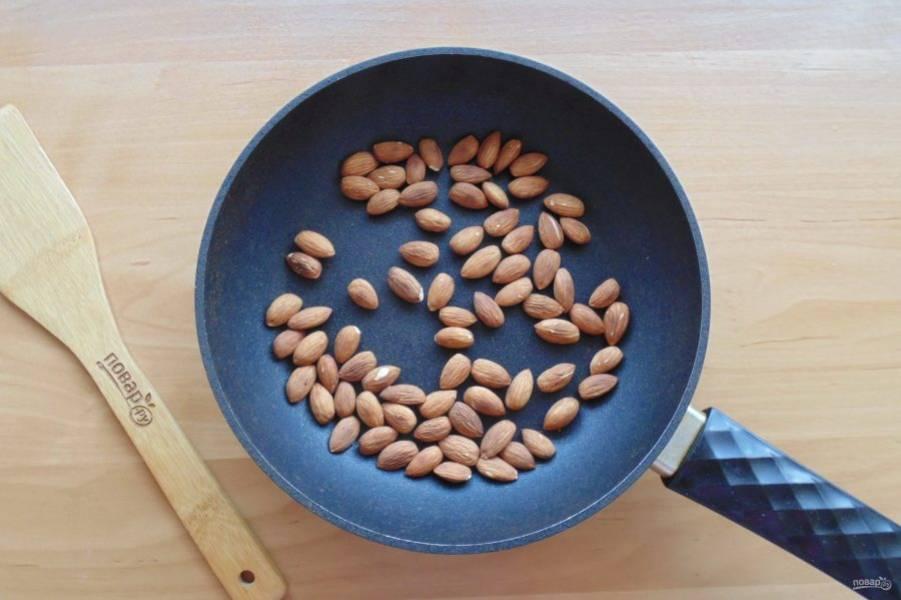 Пока тесто в холодильнике, поджарьте миндаль в сковороде до появления орехового аромата.