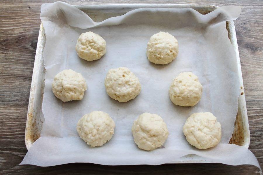 Застелите противень бумагой для выпечки, смажьте руки растительным маслом и сформируйте из теста одинаковые шарики. Выложите на противень на расстоянии.