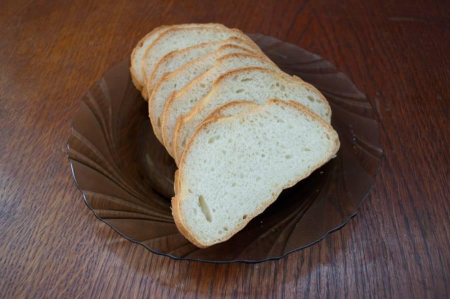 Батон белого хлеба нарезать на равные и ровные кусочки. Ровными они должны быть обязательно, ибо с неровных кусочков будет стекать сыр. Батон можно купить порезанным.