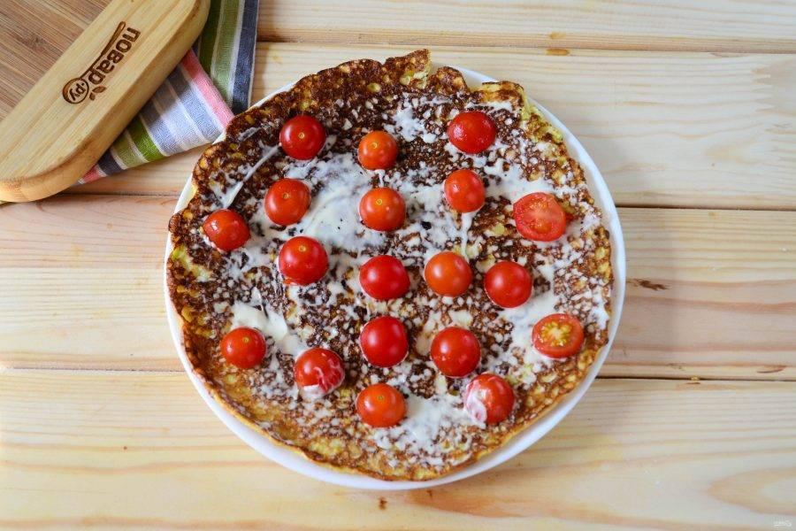 Когда кабачковые блины полностью остынут, начинайте собирать торт. На плоскую тарелку, подходящую по диаметру, положите первый блин. Смажьте его майонезом и выложите дольки помидоров. В этот раз я использовала помидоры черри: просто разрезала их пополам и выкладывала негусто на блин.