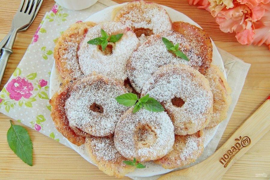 7. Готовые яблоки выкладываем на бумажное полотенце, чтобы убрать излишки масла. По желанию посыпаем десерт сахарной пудрой и корицей. Яблоки в тесте готовы. Приятного аппетита!
