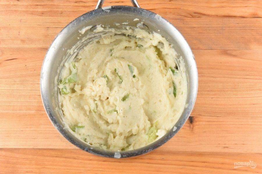 3. Когда картофель будет готов, измельчите его вместе с молоком, зелёной частью лука и натёртым сыром в пюре. Немного молока оставьте для соуса. Добавьте соль в пюре.