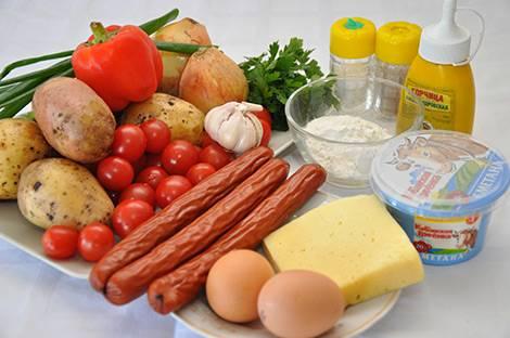Итак, наливаем в сковородку немного растительного масла и обжариваем на нем нарезанный полукольцами лук до золотистого цвета, затем добавляем нарезанный брусками болгарский перец, жарим 3-4 минуты и выкладываем на сковороду нарезанные кружочками копченые колбаски. Перемешиваем все ингредиенты, жарим пару минут и снимаем с огня.