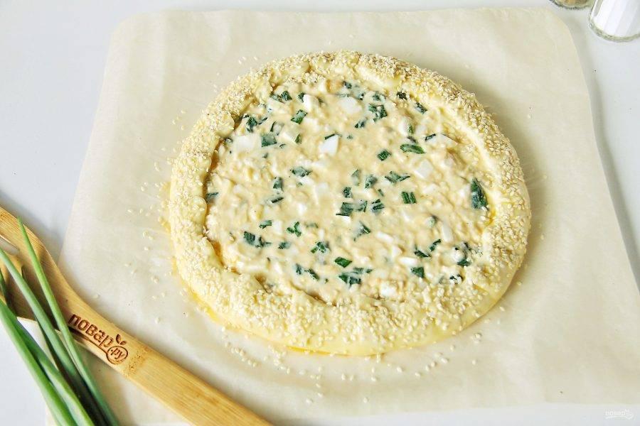 На листе пергамента раскатайте тесто в круг. По центру, отступив немного от краев, выложите начинку. Разровняйте начинку лопаткой и заверните края. Смажьте края пирога желтком и посыпьте кунжутом. Выпекайте при температуре 180 градусов около 30-40 минут.