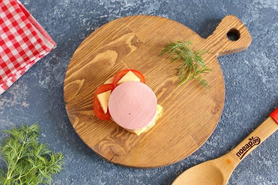Кружочек помидора разрежьте пополам и распределите сверху в виде ушек. На помидор выложите отрезанный ранее сыр как на фото.