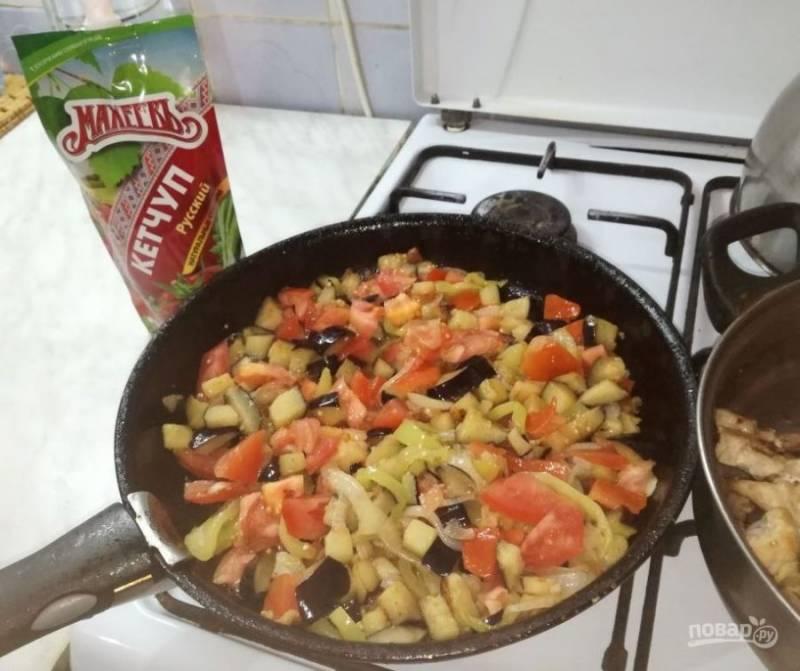 Когда лук станет прозрачным, добавьте баклажан и томат.