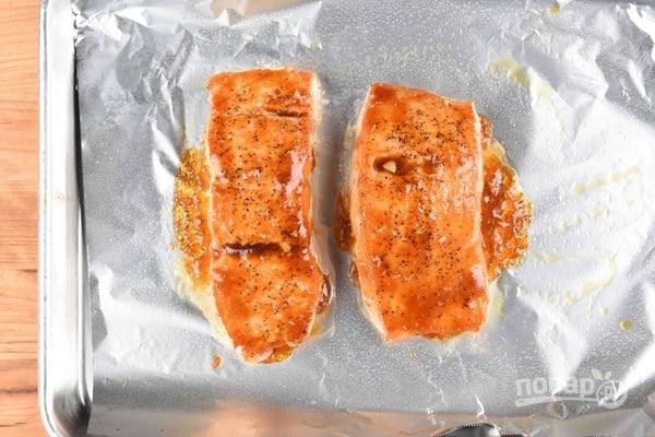 3. Смажьте рыбу перцем и солью. На сковороде разогрейте масло. Обжарьте на нём 3 минуты с каждой стороны лосось. Затем смажьте филе глазурью. После этого отправьте рыбу запекаться при 220 градусах на 6 минут в духовку.