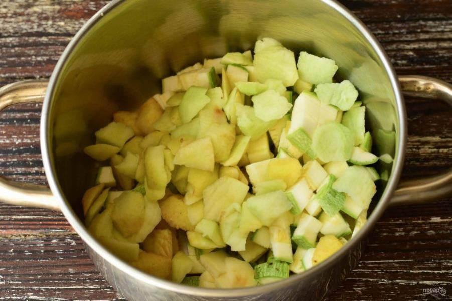 Выложите нарезанные кабачки и яблоки в кастрюлю с толстым дном.