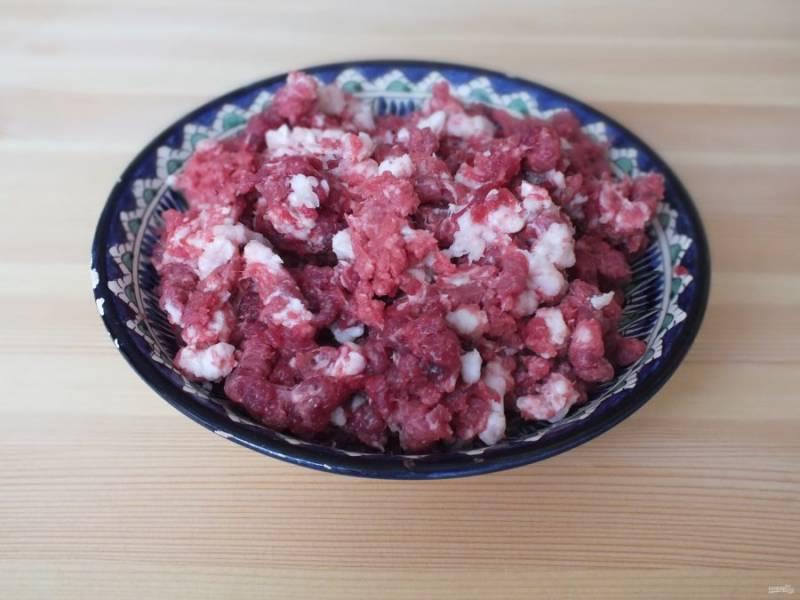 Говядину зачистите от пленок, сухожилий. Измельчите мясо и курдючный жир в ручную с помощью острого ножа или на мясорубке с максимально крупной решеткой.