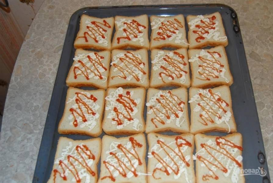 2. Выложите хлеб на противень и смажьте каждый ломтик майонезом и кетчупом.