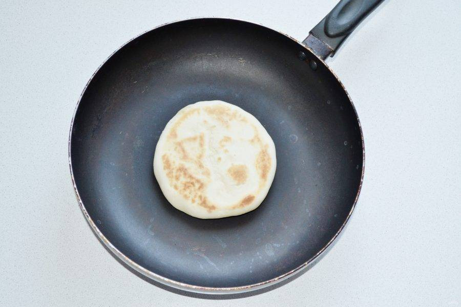 На сухую сковороду выложите лепешку и жарьте под крышкой на среднем огне до румяности с двух сторон.