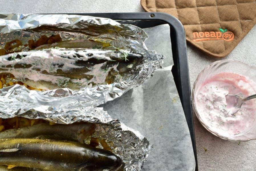 Для соуса соедините измельченный укроп со сметаной, хреном и сливками. Смажьте соусом верх рыбы и продолжайте запекать еще 10-15 минут. До подачи можно закрыть фольгой.