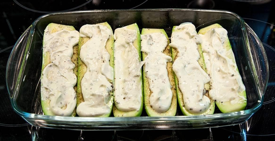 2. В отдельной миске смешаем сметану с измельченным чесноком. Соль - по вкусу. Поливаем этим соусом кабачки, затем отправляем их в духовку запекаться на 30-40 минут.