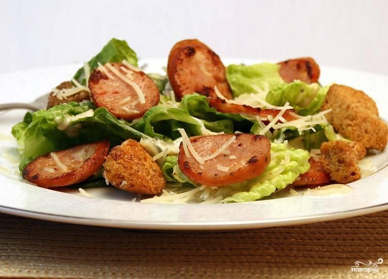 """Выложить на салатные листья колбасу и крутоны, полить остатками соуса и посыпать тертым пармезаном.  Салат """"Цезарь"""" с колбасой готов!"""