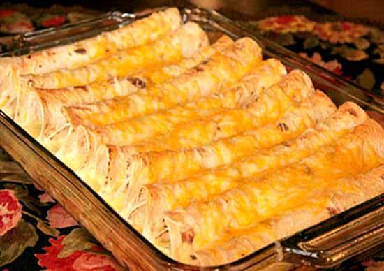 Смазываем противень маслом. Духовку разогреваем до 180 градусов. Укладываем свернутые лаваши рядком плотненько, чтобы не развернулись, в форму. Сверху их можно полить сырным соусом. Ставим запекаться на 15-20 минут.