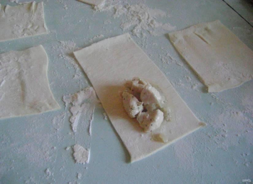 3.Слоеное тесто раскатываю очень тонко, затем нарезаю его небольшими квадратиками. На один край выкладываю куриное мясо и вливаю 1 столовую ложку бульона, в котором готовилась курица.