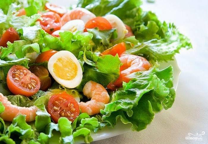 Листья салата крупно порвите руками, выложите на блюдо. В соленой воде отварите креветки, выложите их на салат, добавьте равномерно яйца, помидоры. Посолите по вкусу и сбрызните лимонным соком.