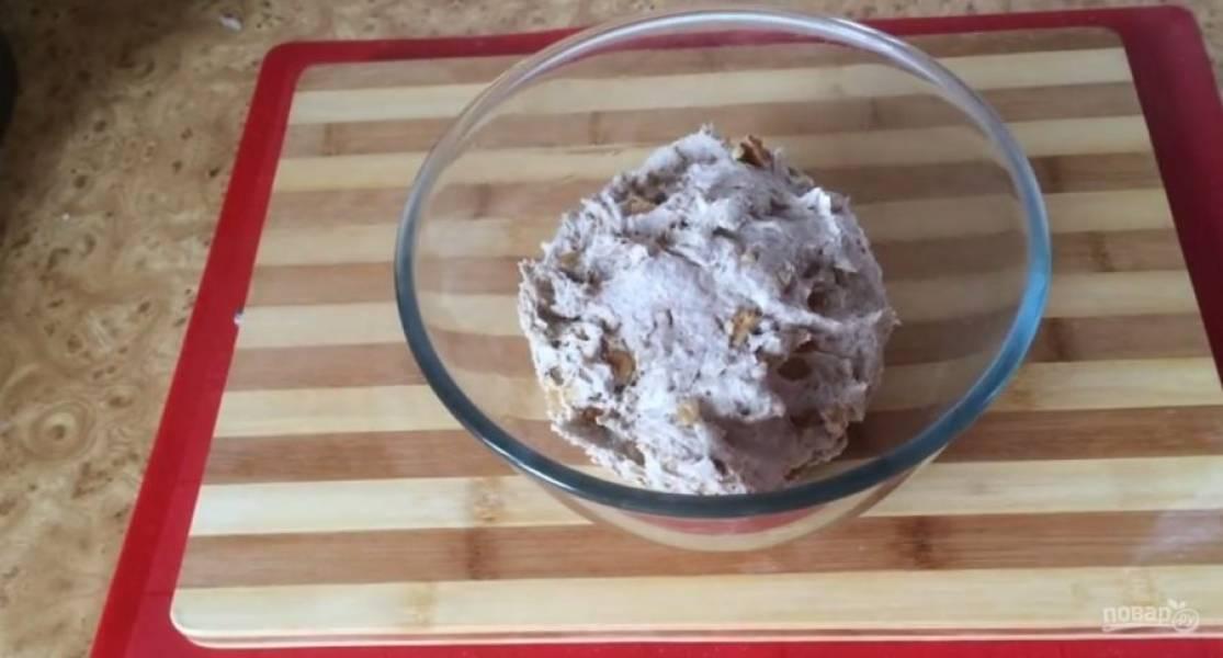 Добавьте грецкие орехи и изюм. Месите до однородности теста. Переложите в миску, смазанную растительным маслом и слегка обомните. Влажными руками выровняйте верх теста и накройте пищевой пленкой.