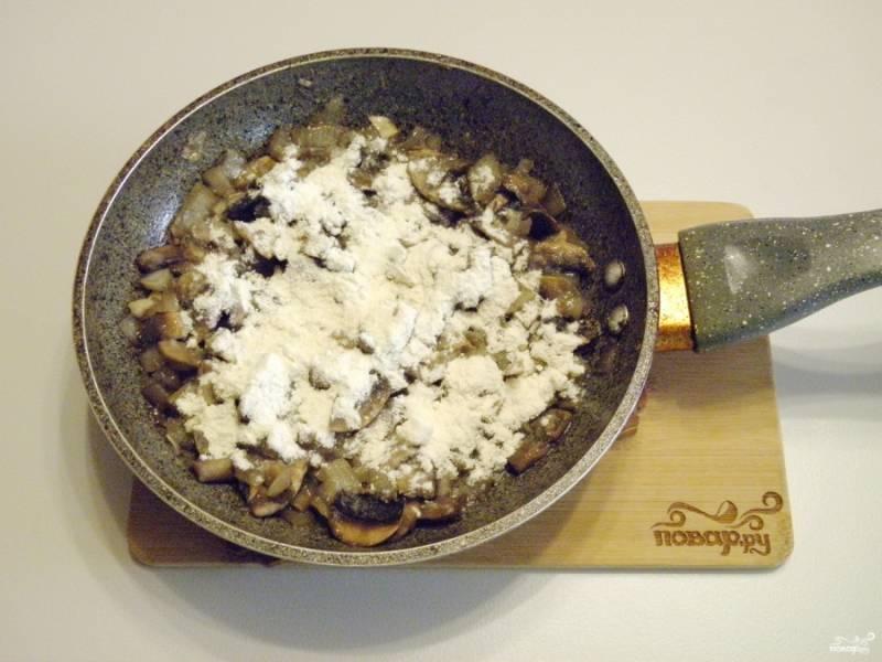 Когда грибы будут полностью готовы, всыпьте муку, перемешайте и обжарьте еще минутку-другую.