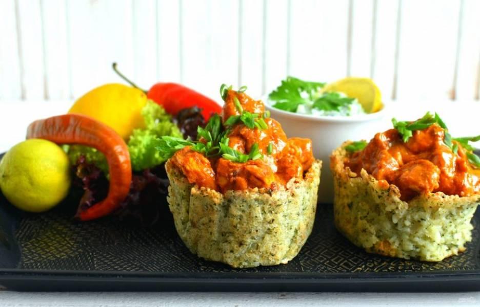 Выложите курицу с соусом в рисовые корзиночки, украсьте зеленью и подавайте горячими с охлажденной райтой. Приятного аппетита!