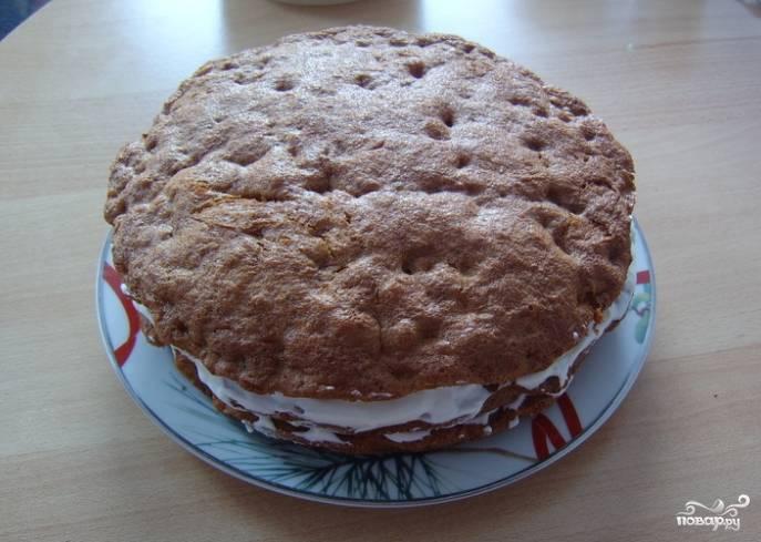 3. Приготовьте крем для смазки коржей. Для этого взбейте сметану, добавив к ней постепенно сливки. Сахарную пудру добавьте в самом конце. Соберите торт, перемазав все слои кремом. Верхний слой тоже смажьте.